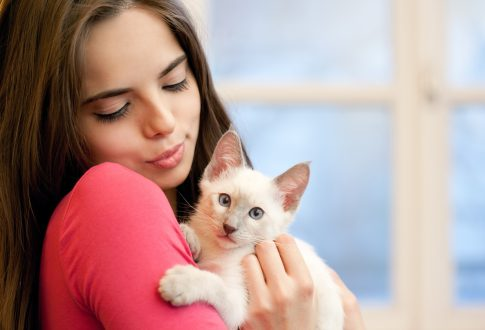 Young adult holding a kitten.