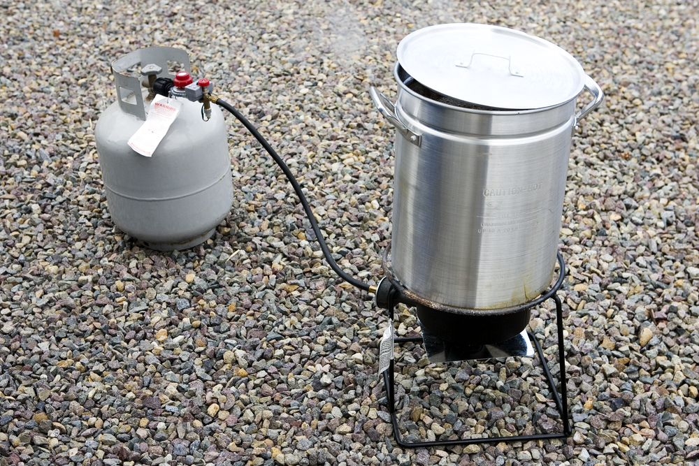 A deep fryer on gravel.
